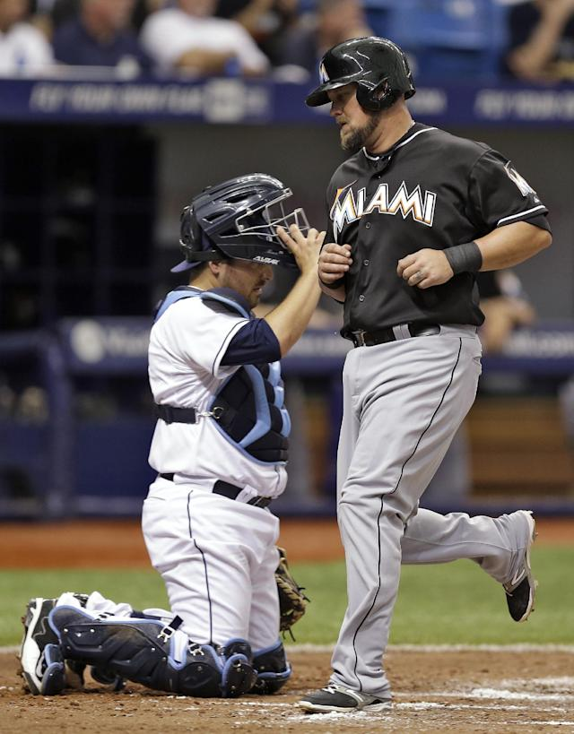 Miami Marlins' Casey McGehee, right, scores in front of Tampa Bay Rays catcher Ali Solis on an RBI single by Marcell Ozuna during the fourth inning of an interleague baseball game Thursday, June 5, 2014, in St. Petersburg, Fla. (AP Photo/Chris O'Meara)