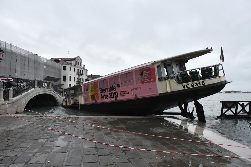 A stranded ferry boat lies on its side, in Venice, Wednesday, Nov. 13, 2019. The mayor of Venice is blaming climate change for flooding in the historic canal city that has reached the second-highest levels ever recorded, as another exceptional water level was recorded Wednesday. The high-water mark hit 187 centimeters (74 inches) late Tuesday, meaning more than 85% of the city was flooded. (AP Photo/Luigi Costantini)