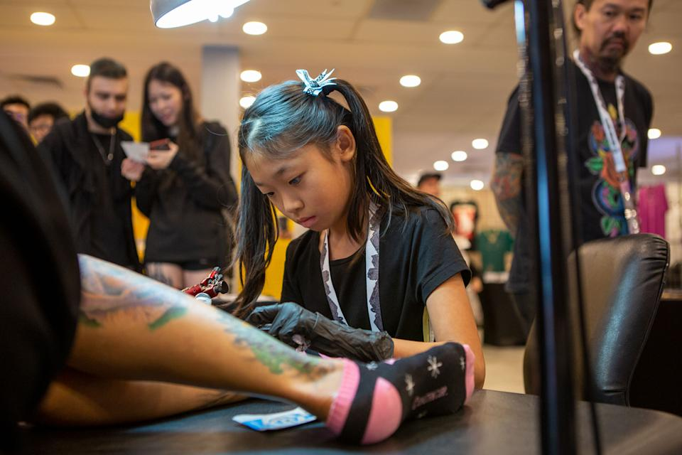 """Lilith, 12, tattooing a customer at the Culture Cartel street culture festival on 7 December. Watch our video: <a href=""""https://bit.ly/2u57B9l"""" rel=""""nofollow noopener"""" target=""""_blank"""" data-ylk=""""slk:https://bit.ly/2u57B9l"""" class=""""link rapid-noclick-resp"""">https://bit.ly/2u57B9l</a> (PHOTO: Dhany Osman / Yahoo Lifestyle Singapore)"""