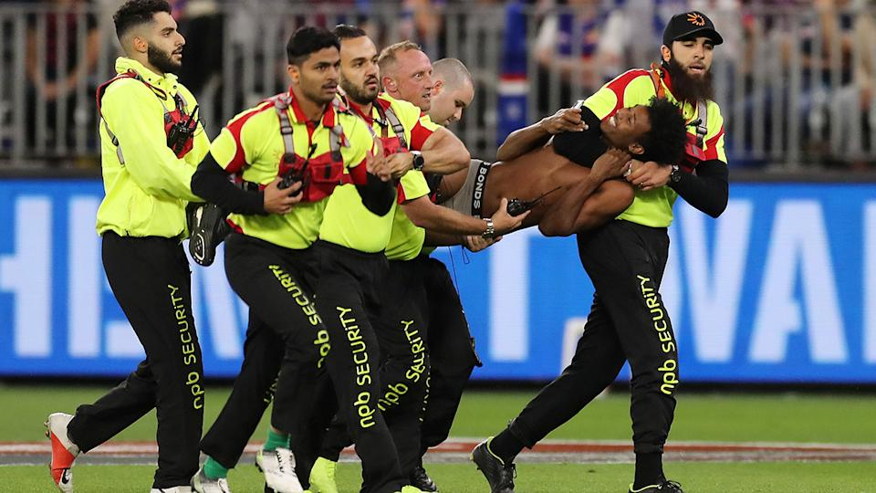A pitch invader, pictured here being tackled by security during the AFL grand final.