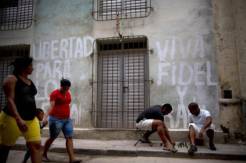 "Men play chess on the sidewalk in front of a wall covered in graffiti that reads in Spanish; ""Long live Fidel and Raul,"" in Havana, Cuba, Thursday, Dec. 19, 2013. In Cuba, revolution is understood as a permanent state. Past, present and future are bound together in a single historical moment: Fidel Castro's triumphant march into Havana in January 1959. (AP Photo/Ramon Espinosa)"