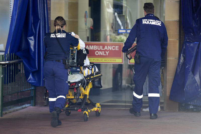 Two paramedics are seen pushing a patient into the hospital.