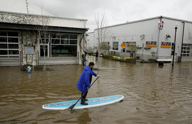 A man uses a paddle board to make his way through the flooded Barlow Market District, Feb. 27, 2019, in Sebastopol, Calif. (Photo: Eric Risberg/AP)