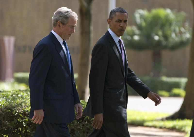 U.S. President Barack Obama, right, walks with former president George W. Bush during a wreath laying ceremony to honor the victims of the U.S. Embassy bombing on Tuesday, July 2, 2013, in Dar es Salaam, Tanzania. The president is traveling in Tanzania on the final leg of his three-country tour in Africa. (AP Photo/Evan Vucci)