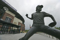 A statue of Atlanta Braves pitcher Phil Niekro stand outside Truist Park, home of baseball's Atlanta Braves, Tuesday, March 31, 2020, in Atlanta. The Braves were suppose to host their home opener on Friday, April 3, but the season's start was postponed by Major League Baseball because of the coronavirus pandemic. (Curtis Compton/Atlanta Journal-Constitution via AP)