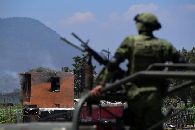 <p>A soldier looks at the site after a series of explosions at fireworks warehouses in Tultepec, central Mexico, on July 5, 2018. – At least 17 people were killed, including rescue workers who died saving others' lives, officials said. The initial explosion occurred around 9:30 am (1430 GMT), then spread to other warehouses just as police and firefighters began attending to the first victims. (Photo: Pedro Pardo/AFP/Getty Images) </p>