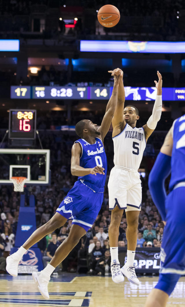 Villanova's Phil Booth, right, shoots a three-point basket against Seton Hall's Quincy McKnight, left, during the first half of an NCAA college basketball game, Sunday, Jan. 27, 2019, in Philadelphia. (AP Photo/Chris Szagola)