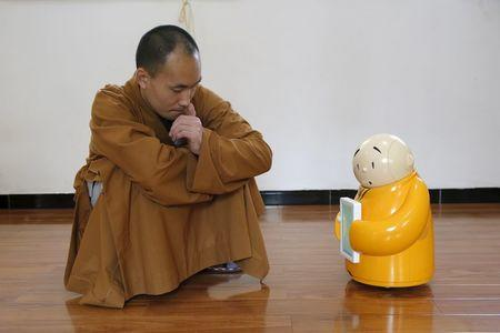 Master Xianfan looks at robot monk Xian'er as he demonstrates the robot's conversation function during a photo opportunity in Longquan Buddhist temple on the outskirts of Beijing