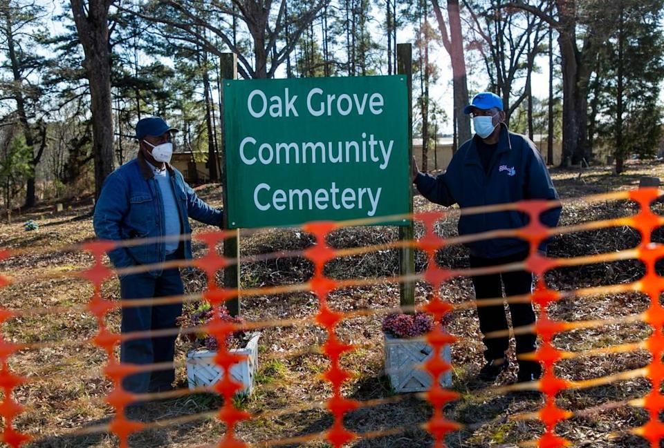 Albert Crenshaw, left, and John Goode stand for a portrait with the sign for the Oak Grove Cemetery, which was founded by freed African-Americans after the Civil War and now has lost more of its tree buffer to widening of the I-440 Beltline, that separated it from the rest of the Method community in the 1960s, on Wednesday, Feb. 17, 2021, in Raleigh, N.C.