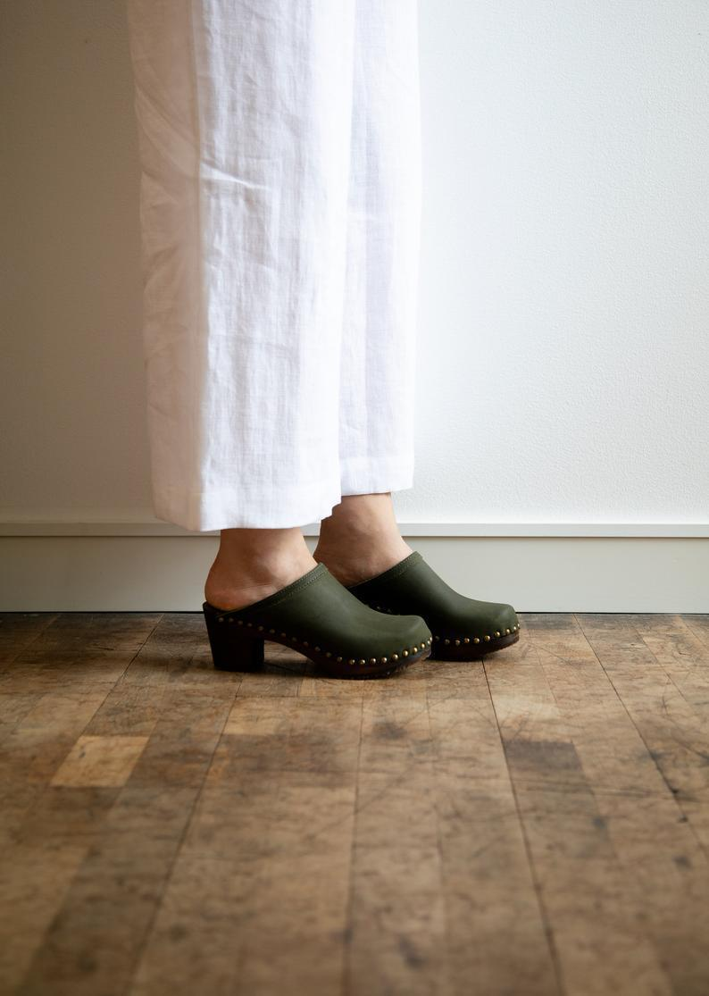 "<h2>Sandgrens Nubuck Leather Clogs</h2><br>Sandgren, a heritage Swedish clog brand that's been in the wooden-footwear biz since 1846, still makes their premium clogs in Sweden — each pair takes a full 24 hours to construct. <br><br><strong>Sandgrens</strong> Olive Wooden Clogs, $, available at <a href=""https://go.skimresources.com/?id=30283X879131&url=https%3A%2F%2Fwww.etsy.com%2Flisting%2F877726951%2Fswedish-wooden-clogs-for-women-sandgrens"" rel=""nofollow noopener"" target=""_blank"" data-ylk=""slk:Etsy"" class=""link rapid-noclick-resp"">Etsy</a>"