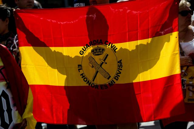 "<p>A demonstrator against independence, holds a Spanish flag reading ""Civil Guard, the honor is my insignia"" during a protest in front of Catalunya Radio headquarters in Barcelona on Sept.27, 2017. Catalonia's regional police force today warned the Spanish government that a demand from the prosecutor's office to seal off polling stations and prevent a contested independence referendum could spark civil unrest. (Photo: Josep Lago/AFP/Getty Images) </p>"