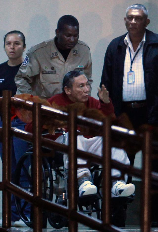 <p>Panama's former strongman, Manuel Noriega, is carried in a wheelchair by a police officer in El Renacer prison on Dec. 11, 2011. On Feb. 5, 2012, Noriega was taken from the prison to Santo Tomas Hospital after he was diagnosed with an apparent brain hemorrhage but recovered and returned to prison. On Jan. 23, 2017, during surgery to remove a brain tumor, he suffered another brain hemorrhage, and he died on May 29, 2017. (AP Photo/Esteban Felix) </p>