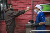 A security guard takes a worker's temperature at the entrance of a fish market in the Villa Maria del Triunfo district on the outskirts of Lima, Peru, Wednesday, May 27, 2020, amid the new coronavirus pandemic. (AP Photo/Rodrigo Abd)