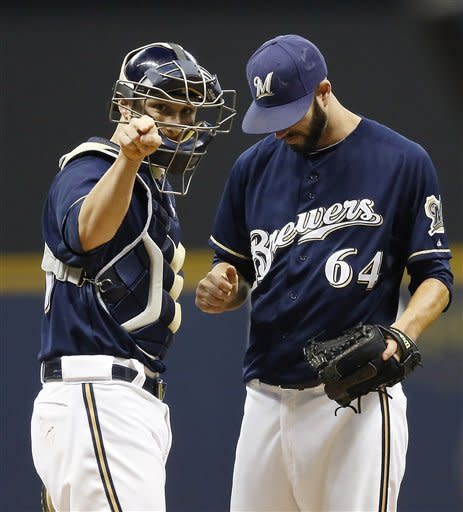 Milwaukee Brewers' Jonathan Lucroy, left, talks with pitcher Mike Fiers during the first inning of a baseball game against the New York Mets, Friday, Sept. 14, 2012, in Milwaukee. (AP Photo/Tom Lynn)