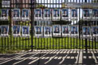 Photographs of the graduating class of 2020 line the fence in front of James Madison High School, Wednesday, May 27, 2020, in the Brooklyn borough of New York. The portraits honor the 750 graduating seniors who may not have the opportunity to step across a graduation stage this year due to the coronavirus pandemic. (AP Photo/Mark Lennihan)