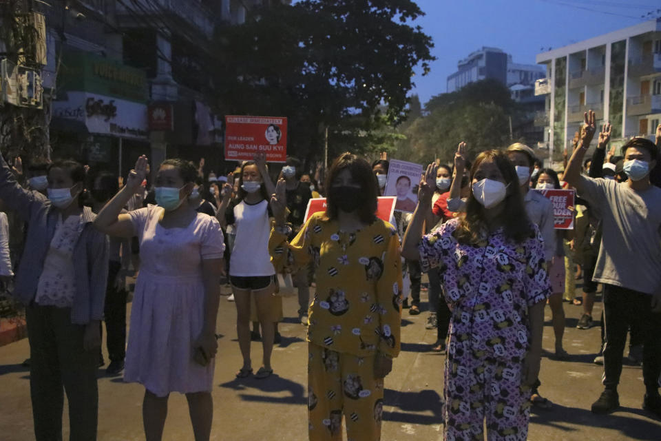 Anti-coup protesters flash three-fingered gesture, a symbol of resistance, during a rally outside their homes in downtown Yangon, Myanmar, Monday, March 22, 2021. Protests against the coup continued in cities and town across the country, including in Mandalay and Yangon. (AP Photo)