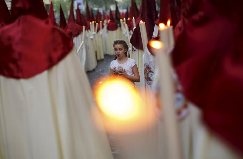 FILE PHOTO: A girl holds ball of wax between penitents of La Lanzada brotherhood during Holy Week in the Andalusian capital of Seville