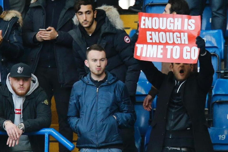 An Arsenal fan holds up a banner calling on Arsenal's French manager Arsene Wenger to quit during the English Premier League football match between Chelsea and Arsenal at Stamford Bridge in London on February 4, 2017 (AFP Photo/)