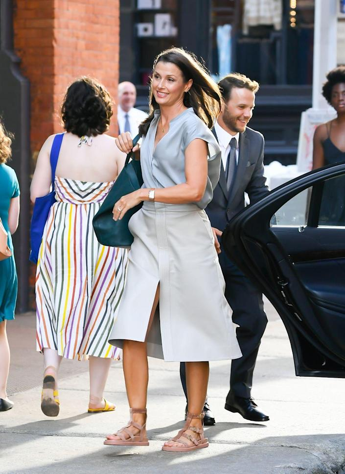 <p>Natasha's Bridget Moynahan made an epic return on the SoHo set in New York City, exiting a black vehicle during filming in a simple blue button-up blouse and a flared khaki pencil skirt, paired with an oversized green bag and sandals. </p>