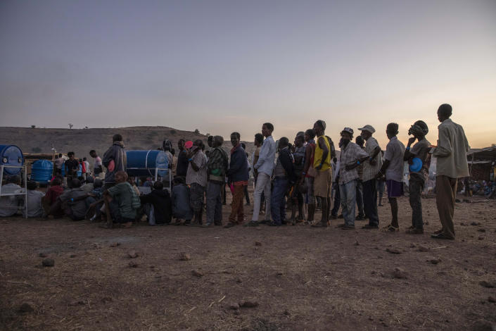 Tigray men who fled the conflict in Ethiopia's Tigray region, stand in line to receive food cooked by Sudanese women volunteers, at Umm Rakouba refugee camp in Qadarif, eastern Sudan, Thursday, Nov. 26, 2020. Ethiopia's prime minister said Thursday the army has been ordered to move on the embattled Tigray regional capital after his 72-hour ultimatum ended for Tigray leaders to surrender, and he warned the city's half-million residents to stay indoors and disarm. (AP Photo/Nariman El-Mofty)