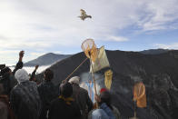 A worshipper throws chicken into the crater of Mount Bromo as an offering to the gods during Yadnya Kasada festival in Probolinggo, East Java, Indonesia, Saturday, June 26, 2021. Every year people gather for the annual festival where offerings of rice, fruit, vegetables, livestock or money are made to Hindu gods at the active volcano to ask for blessings and assure a bountiful harvest. (AP Photo/Trisnadi)