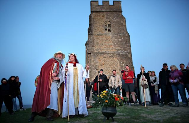GLASTONBURY, ENGLAND - MAY 01: Rollo Maughfling, (L) the Archdruid of Glastonbury and Stonehenge conducts a May Day dawn celebration service in front of St. Michael's Tower on Glastonbury Tor on May 1, 2013 in Glastonbury, England. Although more synonymous with International Workers' Day, or Labour Day, May Day or Beltane is celebrated by druids and pagans as the beginning of summer and the chance to celebrate the coming of the season of warmth and light. Other traditional English May Day rites and celebrations include Morris dancing and the crowning of a May Queen with celebrations involving a Maypole. (Photo by Matt Cardy/Getty Images)