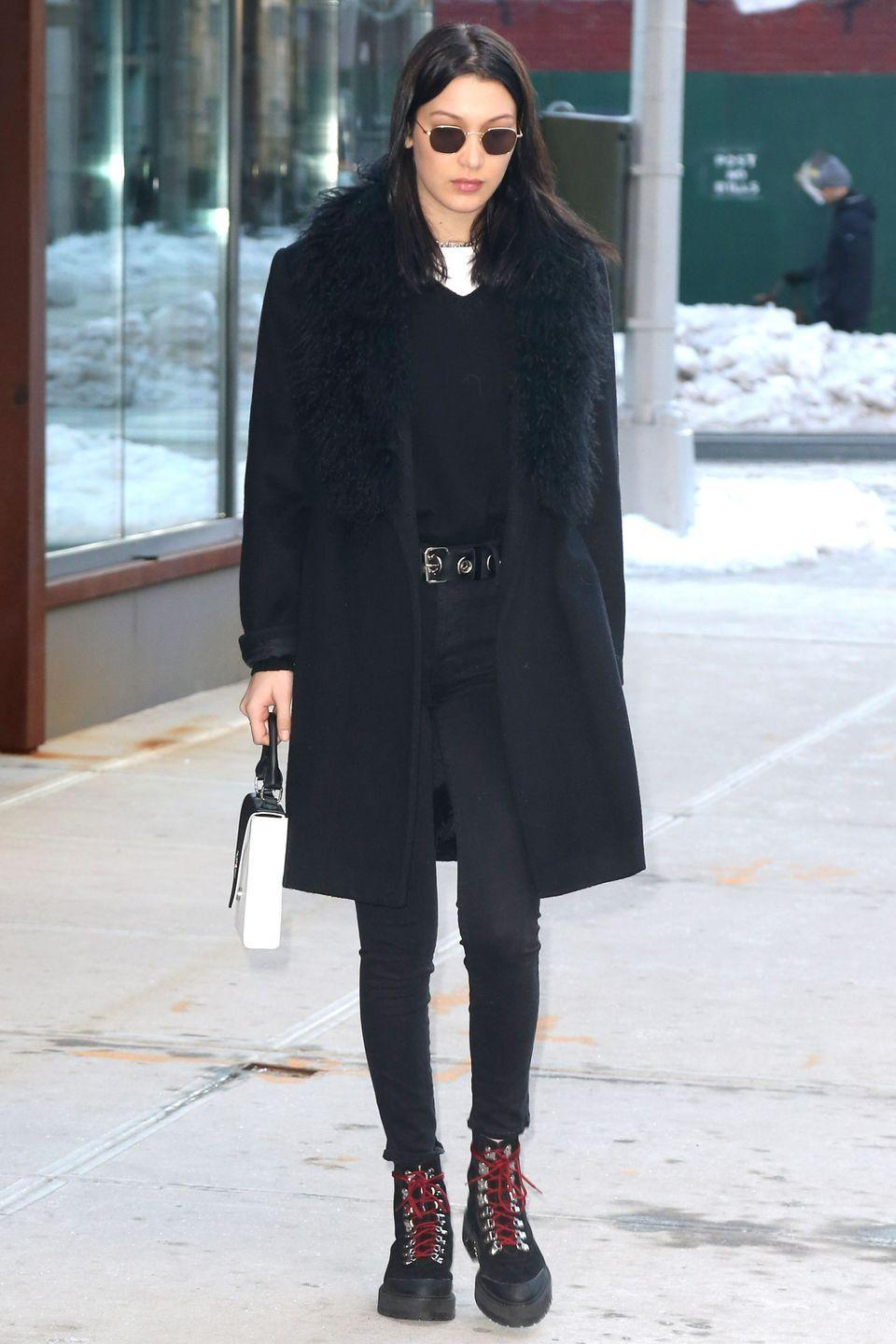 <p>In a black fur coat, skinny jeans, lace-up boots, v-neck sweater, white tee and Krewe rounded sunglasses while out in New York.</p>