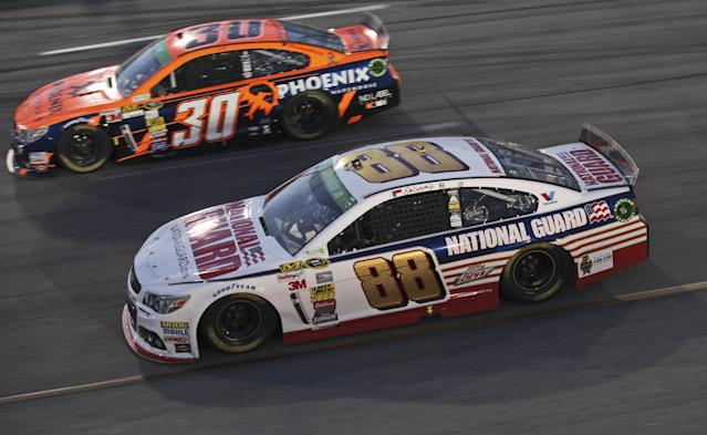 Dale Earnhardt Jr. (88) and JJ Yeley (30) race in Turn 4 during the NASCAR Sprint Cup auto race at Richmond International Raceway in Richmond, Va., Saturday, April 26, 2014. (AP Photo/Zach Gibson)