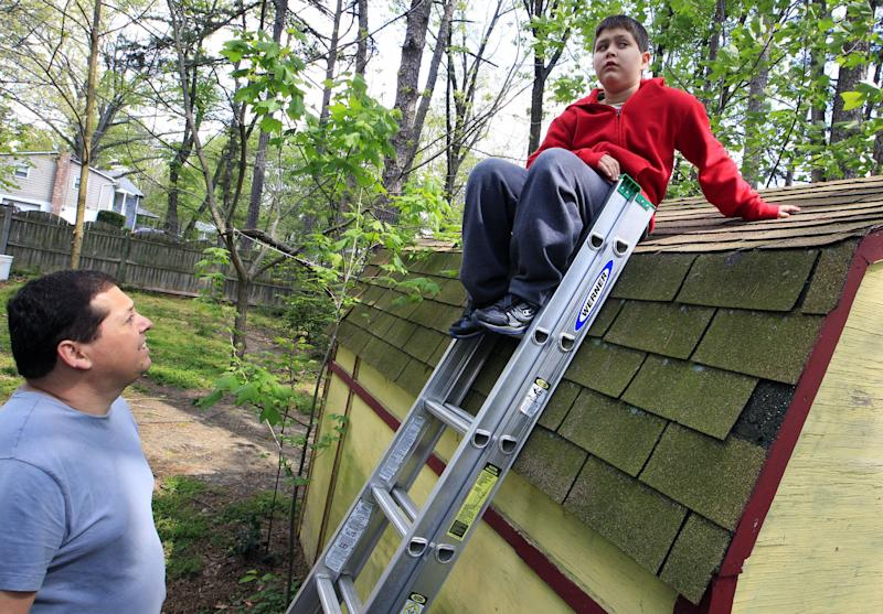 Stuart Chaifetz looks at his son Akian Chaifetz, 10, as he sits on top of a ladder at their home in Cherry Hill, N.J., Wednesday, April 25, 2012. Chaifetz was told that his son Akian was acting violently at his New Jersey school -- including physical assaults against his teacher and teacher's aide -- so he decided to investigate. Akian has autism, as do the rest of the students in the class. This prevented him from being able to explain to his father if anything had been happening to him at school. Chaifetz decided the only way to find out what was behind the outbursts was to send his boy to school wearing a hidden audio recorder. (AP Photo/Mel Evans)