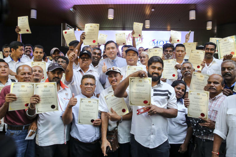 Transport Minister Anthony Loke poses for pictures with taxi drivers holding their offer letters for individual taxi licences at SPAD headquarters in Kuala Lumpur August 30, 2018. — Picture by Yusof Mat Isa