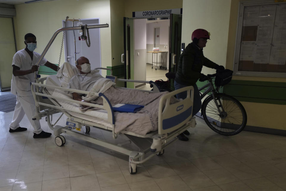 A patient is carried in a bed at the Hospital of Argenteuil, north of Paris, Friday Sept. 25, 2020. France's health agency announced Thursday evening that the country has had 52 new deaths and has detected over 16,000 new cases of coronavirus in 24 hours. (AP Photo/Francois Mori)
