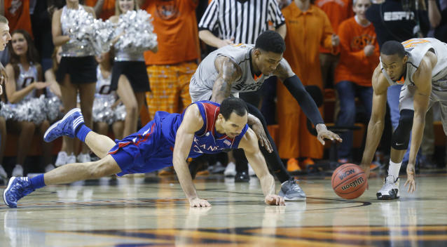 Kansas forward Perry Ellis (34) dives for the loose ball in front of Oklahoma State wing Le'Bryan Nash (2) and wing Markel Brown (22) in the second half of an NCAA college basketball game in Stillwater, Okla., Saturday, March 1, 2014. Oklahoma State won 72-65. (AP Photo/Sue Ogrocki)