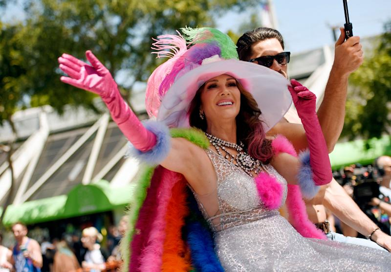 Lisa Vanderpump sits on a parade float waving and holding onto her colorful hat
