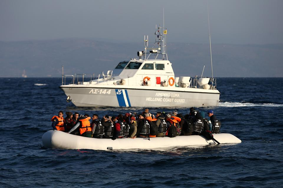 SIKAMINIAS, GREECE - NOVEMBER 17: A Greek coastguard vessel watches a migrant boat as it makes the crossing from Turkey to the Greek island of Lesbos on November 17, 2015 in Sikaminias, Greece. Rafts and boats continue to make the journey from Turkey to Lesbos each day as thousands flee conflict in Iraq, Syria, Afghanistan and other countries. Over 500,000 migrants have entered Europe so far this year and approximately four-fifths of those have paid to be smuggled by sea to Greece from Turkey, the main transit route into the EU. Most of those entering Greece on a boat from Turkey are from the war zones of Syria, Iraq and Afghanistan.  (Photo by Carl Court/Getty Images)