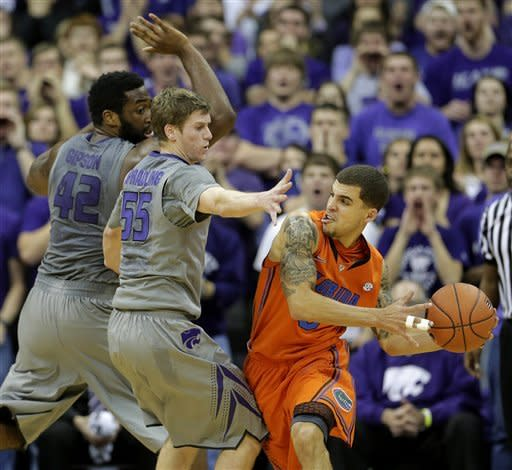 Florida guard Scottie Wilbekin, right, looks for a teammate to pass to as he is pressured by Kansas State guard Will Spradling (55) and forward Thomas Gipson (42)during the first half of an NCAA college basketball game on Saturday, Dec. 22, 2012, at the Sprint Center in Kansas City, Mo. (AP Photo/Charlie Riedel)