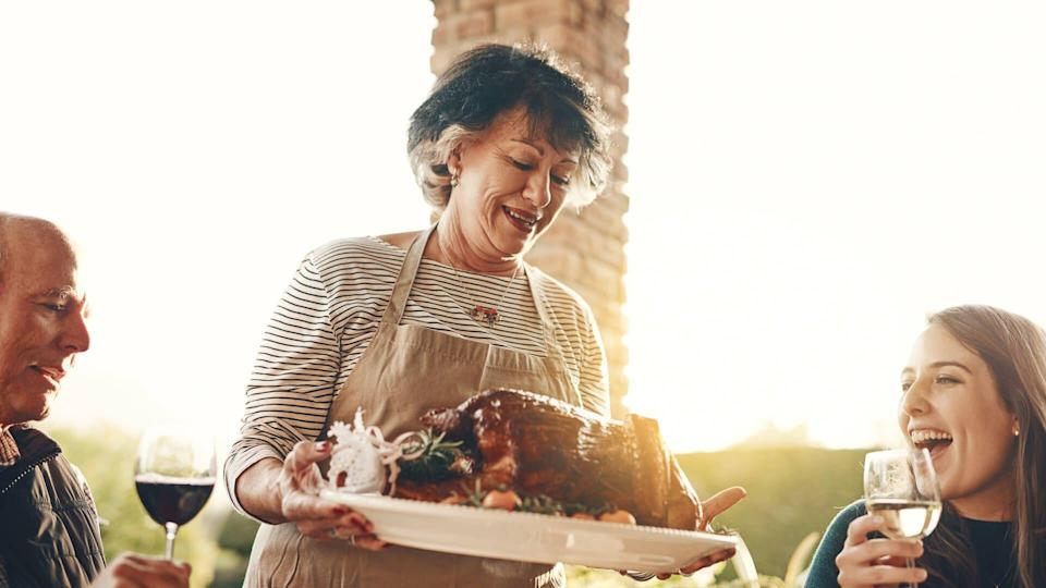 Shot of a senior woman serving roasted chicken at a dinner party.