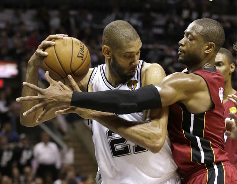 Miami Heat guard Dwyane Wade, right, defends against San Antonio Spurs forward Tim Duncan during the first half at Game 3 of the NBA Finals basketball series, Tuesday, June 11, 2013, in San Antonio. (AP Photo/Eric Gay)