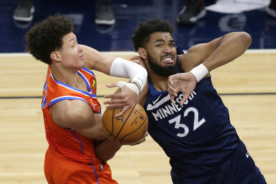 Oklahoma City Thunder center Isaiah Roby (22) pulls a rebound from Minnesota Timberwolves center Karl-Anthony Towns (32) during the second quarter of an NBA basketball game Monday, March 22, 2021, in Minneapolis. (AP Photo/Andy Clayton-King)