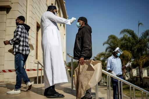 A man carrying a disposable prayer mat has his temperature checked outside the Nizamiye Mosque but many religious leaders say they need more guidance on how to resume worship safely
