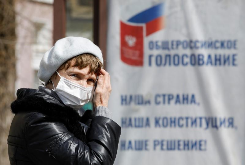 A woman wearing a protective mask near a board informing of a nationwide vote on constitutional changes in Stavropol