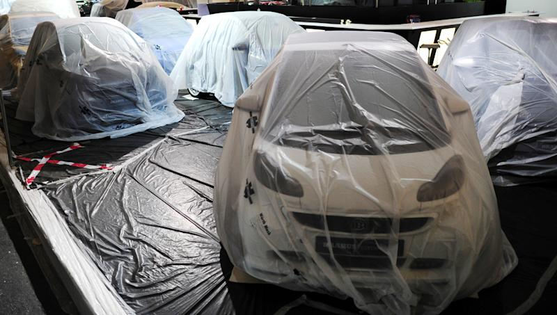 Veiled cars stand on the grounds during preparations for the International Motor Show IAA in Frankfurt, Germany,Sunday Sept. 8, 2013. The 65th IAA features more than 1,000 exhibitors from around the world and takes place from Sept. 12 to Sept. 22 , 2013. (AP Photo/dpa,Boris Roessler)