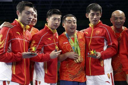 2016 Rio Olympics - Table Tennis - Men's Team - Victory Ceremony - Riocentro - Pavilion 3 - Rio de Janeiro, Brazil - 17/08/2016. Gold medallists Ma Long (CHN) of China, Xu Xin (CHN) of China and Zhang Jike (CHN) of China pose with their coach Liu Guoliang and other members of their team on the podium.            REUTERS/Alkis Konstantinidis