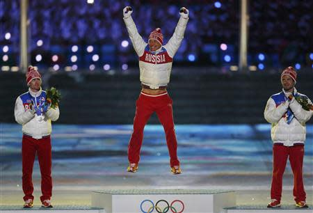 Russia's gold medallist Alexander Legkov jumps on the podium between compatriots silver medallist Maxim Vylegzhanin (L) and bronze medallist Ilia Chernousov (R) as they are presented with medals for the men's cross-country 50km mass start free event during the closing ceremony of the 2014 Sochi Winter Olympics, February 23, 2014. REUTERS/Phil Noble