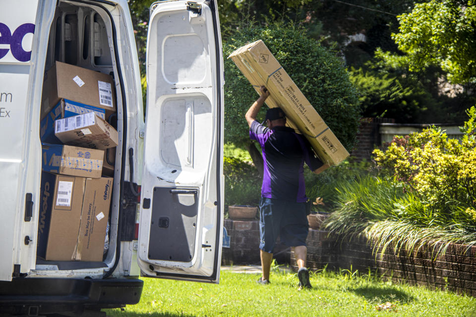 07-14-2020 Tulsa USA Delivery man carries large box above head with back door to van open showing many more boxes in leafy neighborhood