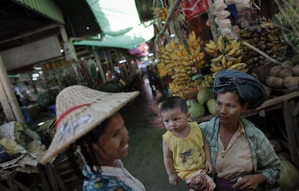 Women chat at a market in capital Naypyitaw, January 24, 2012.