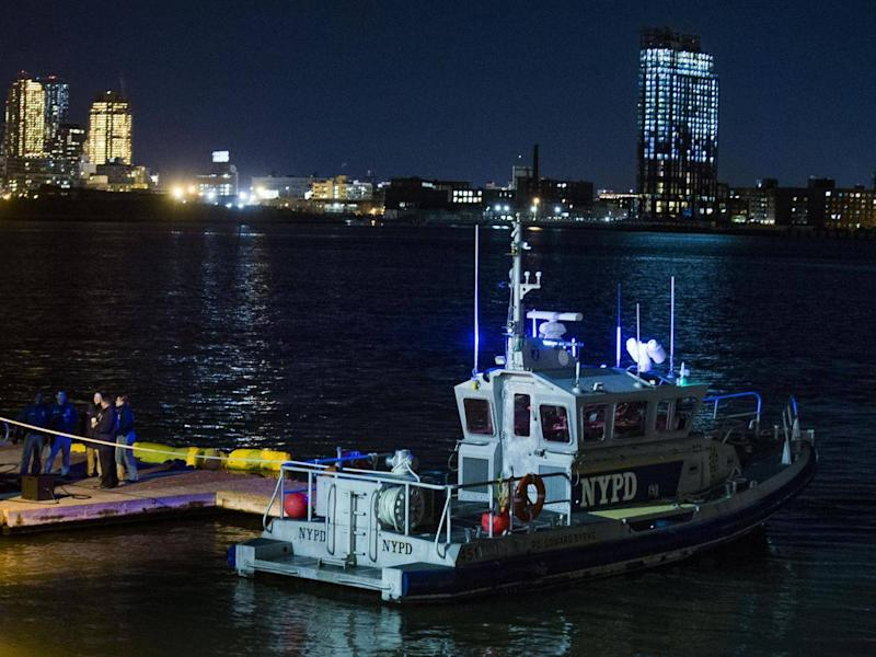 Yellow buoys that a New York police officer said are suspending the helicopter that crashed on the East River float next to a NYPD police boat. (AP Photo/Andres Kudacki)