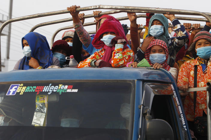 Garment workers stand on a truck as they head to work outside Phnom Penh, Cambodia, Thursday, May 6, 2021. Cambodia on Thursday ended a lockdown in the capital region. (AP Photo/Heng Sinith)