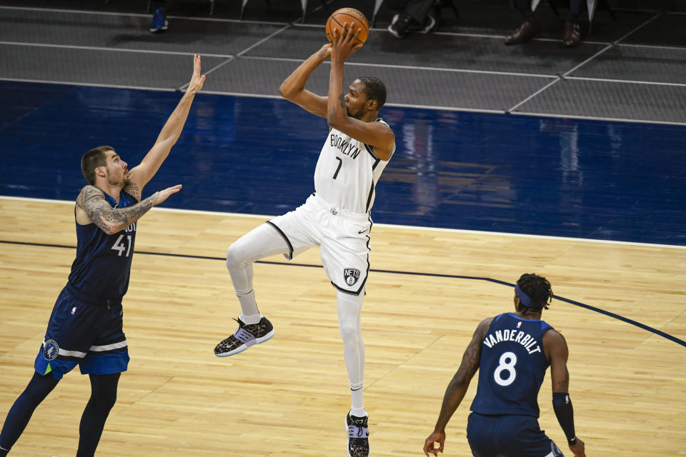 Brooklyn Nets forward Kevin Durant(7) shoots over Minnesota Timberwolves forward Juancho Hernangomez (41) as Timberwolves forward Jarred Vanderbilt (8) watches during the second half of an NBA basketball game Tuesday, April 13, 2021, in Minneapolis. The Nets won 127-97. (AP Photo/Craig Lassig)