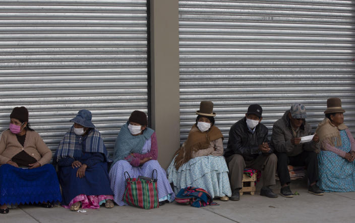 Senior citizens, most wearing protective face masks, wait in a line to receive their monthly pension in La Paz, Bolivia, Thursday, April 9, 2020, where the government has restricted residents to essential shopping in the mornings in an attempt to contain the spread of the new coronavirus. (AP Photo/Juan Karita)