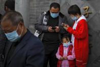 A child wearing a face mask to help curb the spread of the coronavirus looks as masked people browsing their smartphones near Forbidden City in Beijing, Sunday, Oct. 25, 2020. With the outbreak of COVID-19 largely under control within China's borders, the routines of normal daily life have begun to return for its citizens. (AP Photo/Andy Wong)